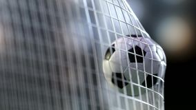 在目标网的足球与慢动作 在网的慢动作橄榄球球