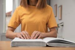 在盲人识字系统写的瞎的妇女看书在桌上 库存照片