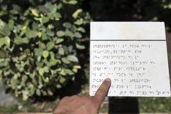 在盲人识字系统语言的盲目的读书文本说明在庭院 图库摄影