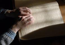 在盲人识字系统的盲目的读书文本 读b的人的手特写镜头  免版税库存照片