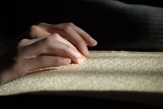 在盲人识字系统的盲目的读书文本 读b的人的手特写镜头  免版税图库摄影