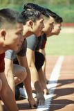 在直线的幼小亚洲赛跑者 图库摄影