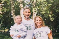 在相同T恤杉的特写镜头幸福家庭有-家庭队,妈妈,爸爸-拥抱在公园的数字和题字的 免版税库存照片