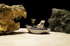在看与绿色玉石头的小船的一个寻宝人黄色水晶石头 库存照片