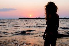 在看令人惊讶的日出的泳装的妇女形象在海附近在海滩 免版税库存图片