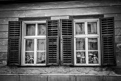 在看和观察您的窗口的Creppy小的玩偶 免版税库存图片