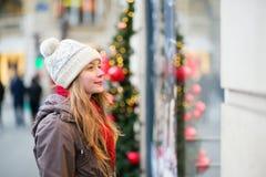 在看商店窗口的一条巴黎人街道上的女孩 库存照片