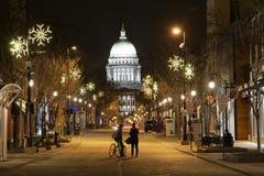 在看国会大厦的街道的夫妇在一个多雪的晚上在麦迪逊, WI 免版税库存照片