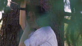 在看在照相机的树附近的俏丽的妇女身分,美好的女性慢动作 股票录像