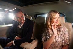 在看在窗口外面的大型高级轿车背后的年轻夫妇 图库摄影