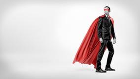 在看在他的在白色背景的肩膀的流动的红色超级英雄海角和面具的一个商人 库存照片