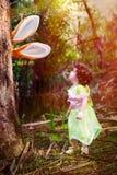 在看它的树和小女孩后的兔宝宝耳朵 免版税图库摄影