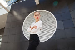 在看对几何现代大厦墙壁的女衬衫和裙子的有吸引力的模型 免版税库存图片