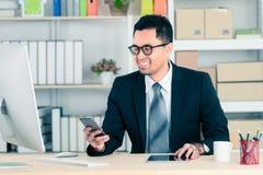 在看对智能手机和sitti的衣服微笑的亚洲商人 免版税库存照片