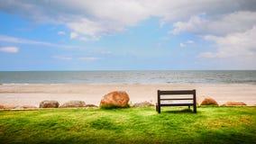 在看对海洋的一个白色沙子海滩附近的一个长木凳 库存照片