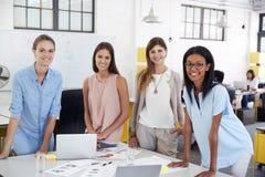 在看对照相机的办公桌的女性企业队立场 免版税库存图片
