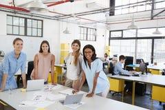 在看对照相机的办公桌的女性企业队立场 库存照片
