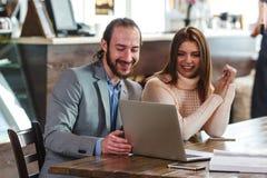 在看对膝上型计算机的咖啡馆的夫妇 免版税库存图片