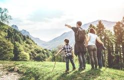 在看山全景的一个绿色草甸的家庭 免版税库存照片