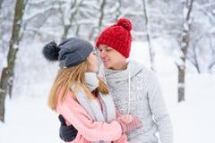 在看彼此的爱的夫妇在降雪期间 免版税库存照片