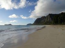 在看往兔子和岩石海岛的黄昏的Waimanalo海滩 图库摄影