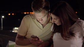 在看智能手机纸卷的街道上的晚上结合浏览 股票视频
