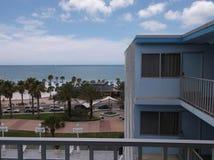 在看棕榈树和海洋的旅馆阳台 库存照片