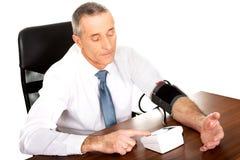 在看法商人测量的血压上 免版税图库摄影