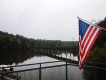 在看湖的美国国旗和桥梁落后 免版税库存图片