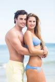 在看照相机和拥抱的泳装的愉快的夫妇 库存照片
