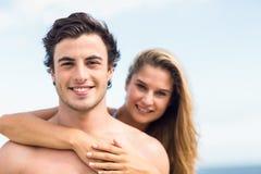 在看照相机和拥抱的泳装的愉快的夫妇 免版税库存照片