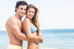 在看照相机和拥抱的泳装的愉快的夫妇 免版税库存图片