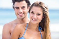 在看照相机和拥抱的泳装的愉快的夫妇 库存图片