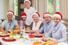 在看照相机的圣诞老人帽子的家庭圣诞节时间 免版税库存照片