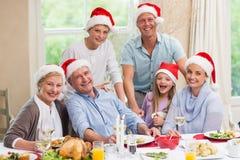 在看照相机的圣诞老人帽子的愉快的家庭 库存图片