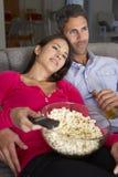 在看电视和吃玉米花的沙发的西班牙夫妇 免版税库存图片