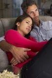 在看电视和吃玉米花的沙发的西班牙夫妇 库存图片
