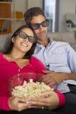 在看电视的沙发的夫妇戴3D吃玉米花的眼镜 图库摄影