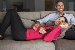 在看电视的沙发的西班牙夫妇 免版税库存照片