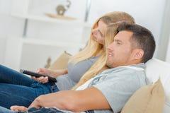 在看电视的长沙发的侧视图夫妇 免版税库存照片