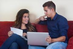 在看票据的长沙发的婚姻 免版税库存照片