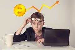 在看膝上型计算机的玻璃的年轻嬉戏的企业孩子 Bitcoins -位硬币BTC与图的新的真正金钱 免版税图库摄影