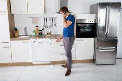 在看见泡沫冲击的人从洗碗机出来 库存照片