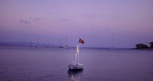 在看见的一条小的小船在桃红色日落 库存照片