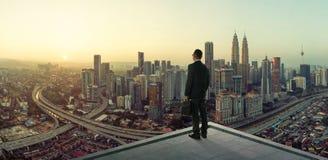 在看起来巨大都市风景视图的屋顶的商人立场 库存照片
