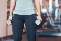 在看起来愉快和运作在她的二头肌的健身房的强的女子举重 图库摄影