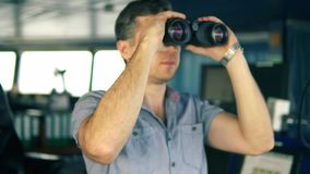 在看通过双筒望远镜的航行手表期间的官员 股票录像