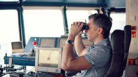 在看通过双筒望远镜的航行手表期间的官员 影视素材