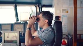 在看通过双筒望远镜的航行手表期间的官员 股票视频