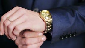 在看他的手表的衣服的男性商人 股票视频